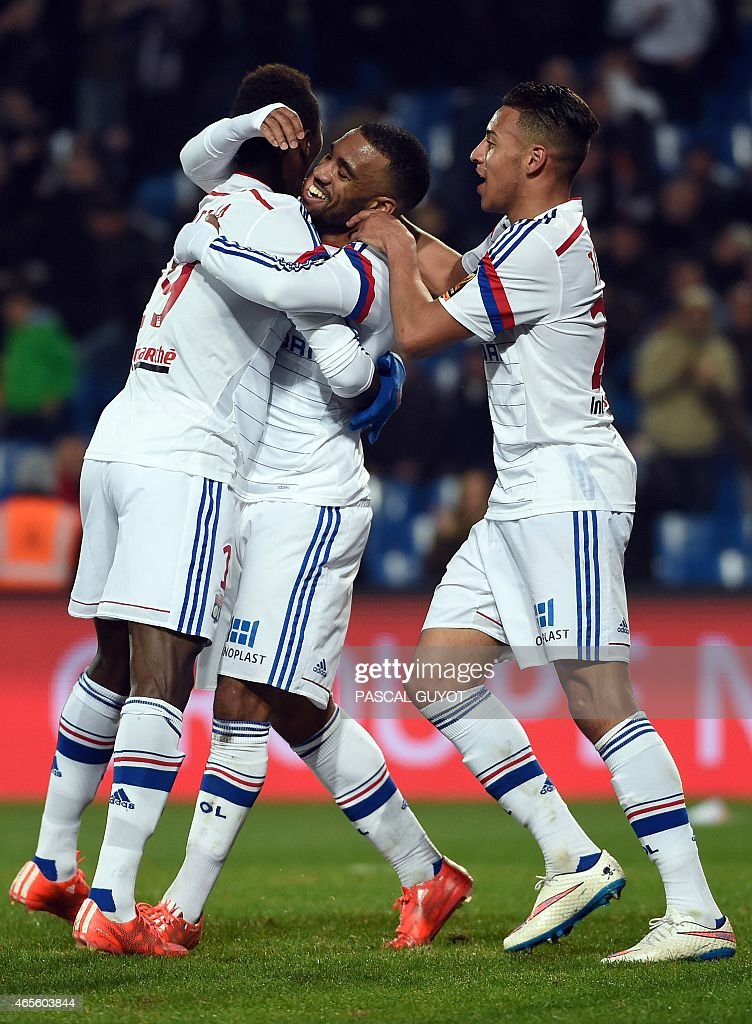 Lyon's French forward Alexandre Lacazette (C) is congratuled by teammates after scoring a goal during the French L1 football match between Montpellier and Lyon on March 8, 2015 at the La Mosson Stadium in Montpellier, southern France.
