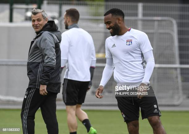 Lyon's French forward Alexandre Lacazette jokes with Lyon's French head coach Bruno Genesio during a training session on the eve of the Europa League...