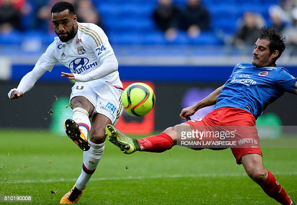 Lyon's French forward Alexandre Lacazette kicks the ball next to Caens French midfielder Nicolas Seube during the French L1 football match between...