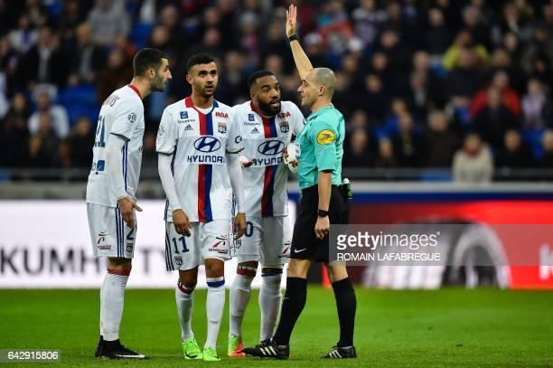 Lyon's French forward Alexandre Lacazette Lyon's Algerian forward Rachid Ghezzal and Lyon's French midfielder Maxime Gonalons argue with the referee...
