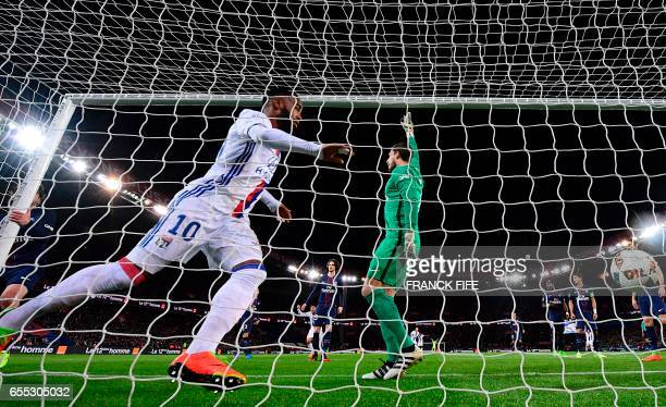 Lyon's French forward Alexandre Lacazette scores the opening goal as Paris SaintGermain's German goalkeeper Kevin Trapp reacts during the French L1...
