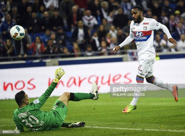 Lyon's French forward Alexandre Lacazette shoots and scores his 100th goal in Ligue 1 past Nice's French goalkeeper Yoann Cardinale during the French...