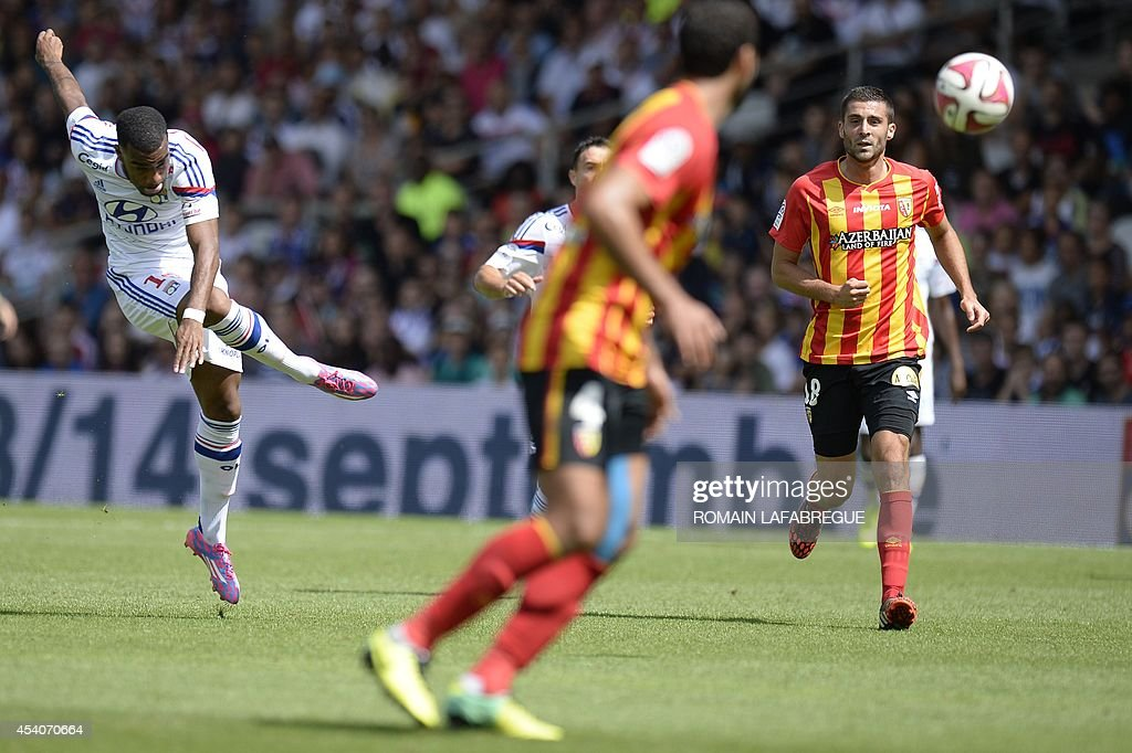 Lyon's French forward Alexandre Lacazette (L) shoots the ball in front of Lens' French midfielder Pierrick Valdivia (R) during the French L1 football match between Lyon (OL) against Lens (RCL) at the Gerland stadium in Lyon, central-eastern France, on August 24, 2014.