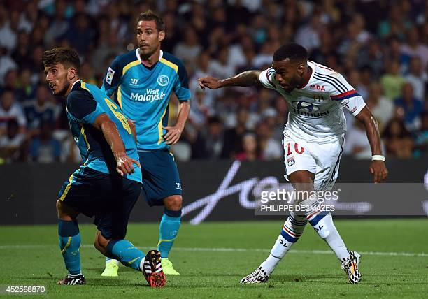 Lyon's French forward Alexandre Lacazette vies against Sevilla's Spanish defender Fernando Navarro and Spanish defender Daniel Carrico during the...