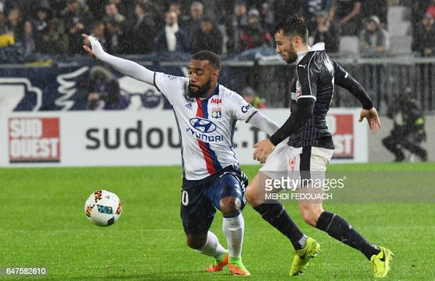 Lyon's French forward Alexandre Lacazette vies for the ball with Bordeaux's Serbian defender Milan Gajic during the French L1 footbal match between...