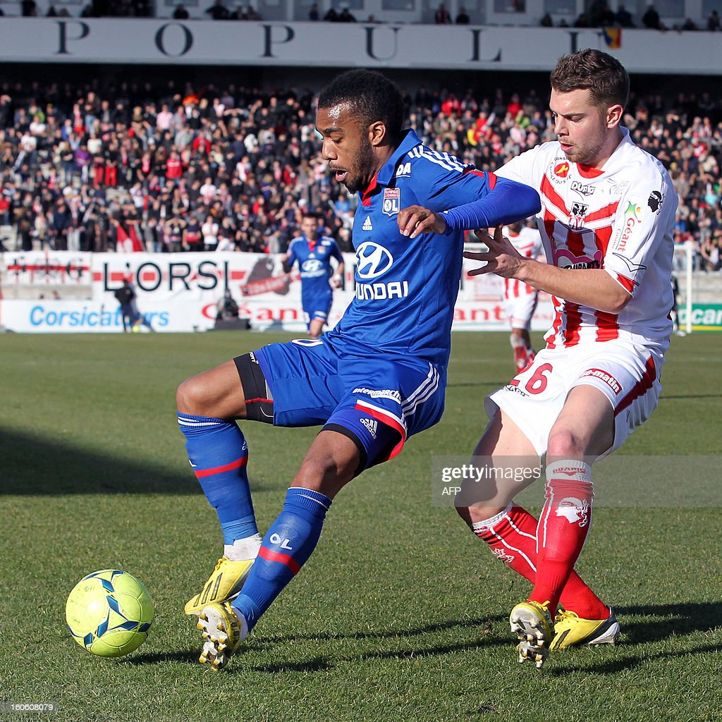 Lyon's French forward Alexandre Lacazette (L) vies with Ajaccio's French defender Samuel Bouhours during the French L1 football match Ajaccio (ACA) vs Lyon (OL) in the Francois Coty stadium in Ajaccio, French Mediterranean island of Corsica, on February 3, 2013.