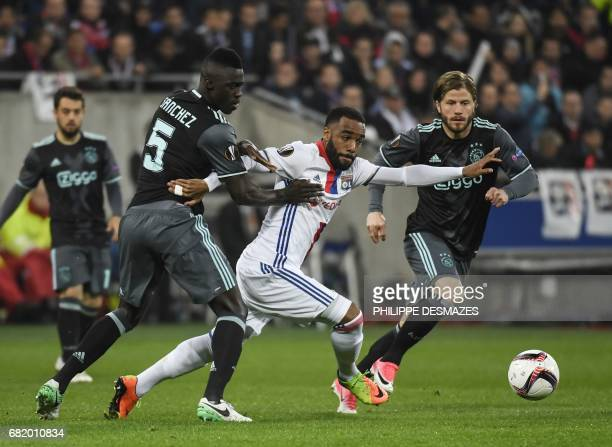 Lyon's French forward Alexandre Lacazette vies with Ajax' Colombian defender Davinson Sánchez and Ajax' Danish forward Lasse Schone during the Europa...