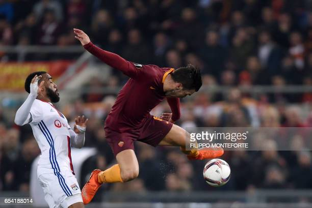 Lyon's French forward Alexandre Lacazette vies with AS Roma's Dutch midfielder Kevin Strootman during the Europa League Round of 16 second leg...