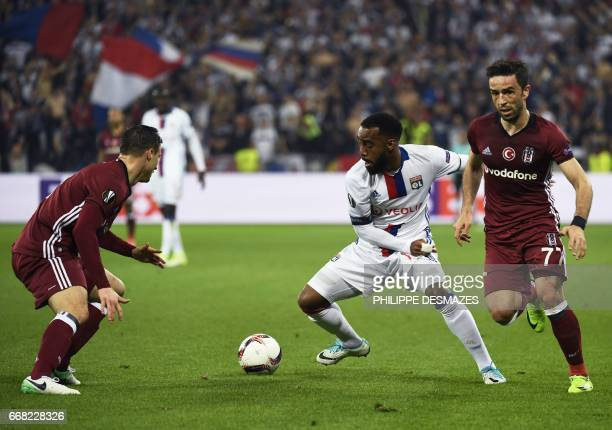 Lyon's French forward Alexandre Lacazette vies with Besiktas' Serbian defender Dusko Tosic and Besiktas' Turkish defender Gokhan Gonul during the...