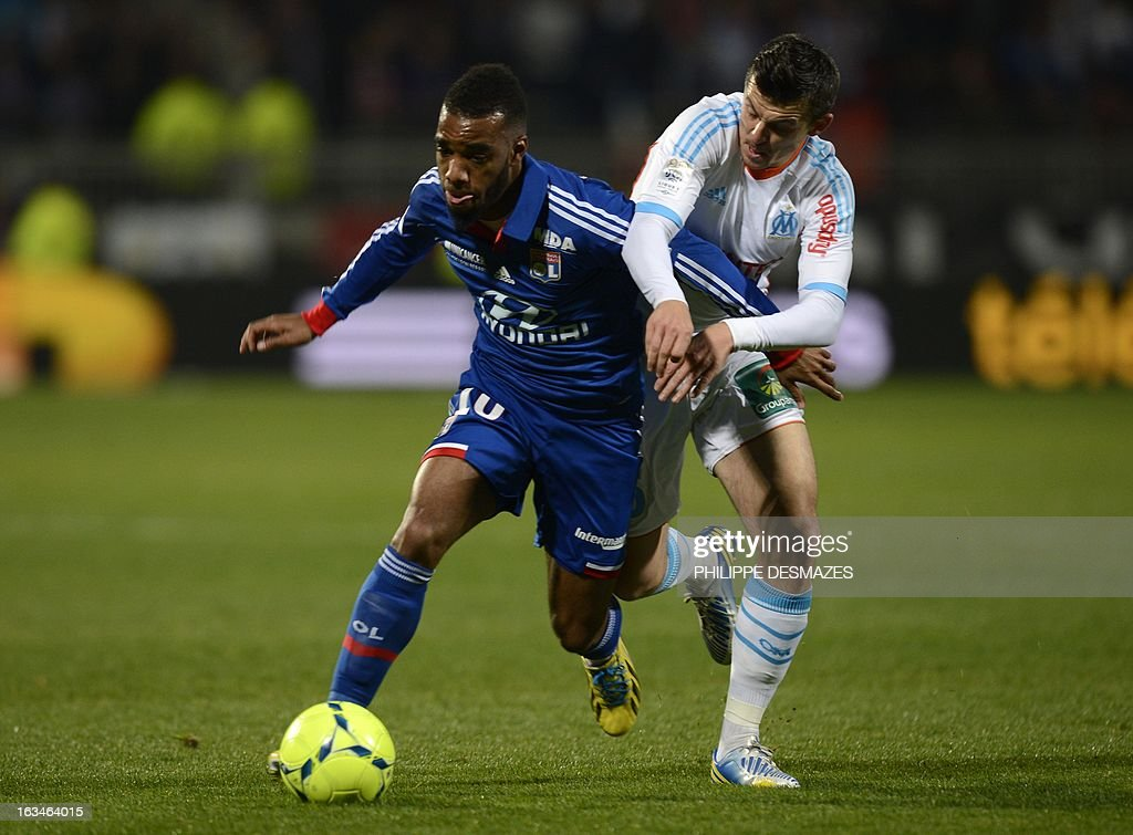 Lyon's French forward Alexandre Lacazette (L) vies with Marseille's British midfielder Joseph Barton (R) during the French L1 football match Olympique Lyonnais (OL) vs Olympique de Marseille (om) on March 10, 2013 at the Gerland stadium in Lyon, southeasthern France.
