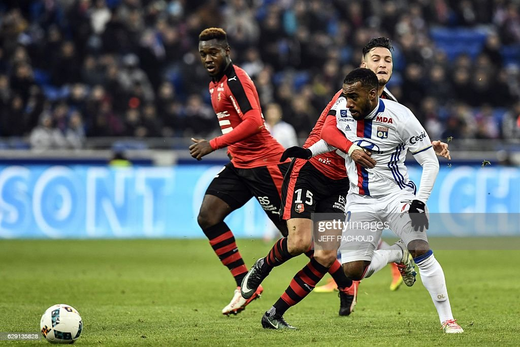 Lyon's French forward Alexandre Lacazette (R) vies with Rennes'Algeria defender Ramy Bensebaini (L) during the French L1 football match Olympique Lyonnais (OL) vs Rennes (Stade Rennais) on December 11, 2016, at the Parc Olympique Lyonnais stadium in Decines-Charpieu, central-eastern France. / AFP / JEFF
