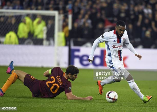 Lyon's French forward Alexandre Lacazette vies with Roma's Italian defender Federico Fazio during the Europa League round of 16 first leg football...