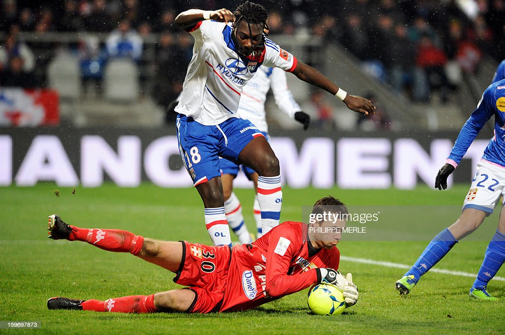 Lyon's French forward Bafetimbi Gomis (Top) vies for the ball with Evian's Danish goalkeeper Stephan Andersen during the French L1 football match between Lyon and Evian on January 18, 2013, at the Gerland stadium in Lyon.