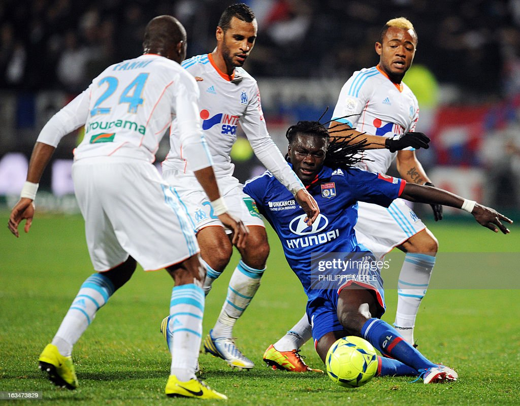 Lyon's French forward Bafetimbi Gomis (C) vies for the ball with Marseille's players during the French L1 football match Lyon vs Marseille on March 10 , 2013 at the Gerland stadium in Lyon.