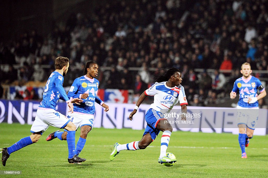 Lyon's French forward Bafetimbi Gomis (C) vies with Evian's players during the French L1 football match Lyon (OL) vs Evian (ETG FC) on January 18, 2013 at the Gerland stadium in Lyon.