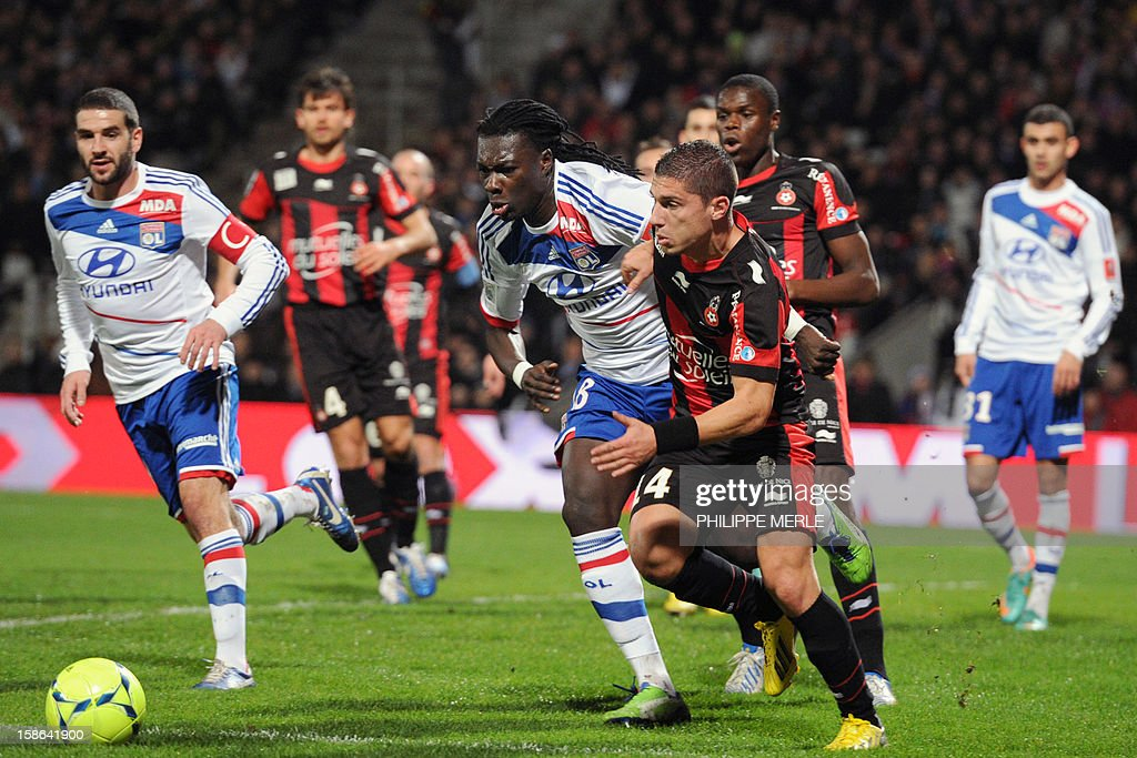Lyon's French forward Bafetimbi Gomis (C) vies with Nice's Serbian defender Nemanja Pejcinovic (C-R) during the French L1 football match Lyon vs Nice, on December 22, 2012 at the Gerland stadium in Lyon, central eastern France.