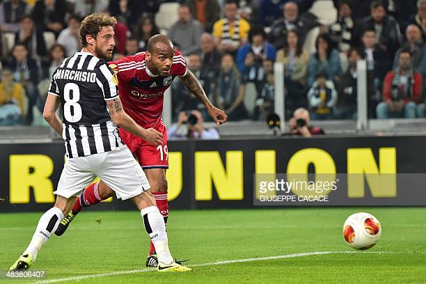 Lyon's French forward Jimmy Briand heads the ball and scores against Juventus' midfielder Claudio Marchisio during the UEFA Europa League...