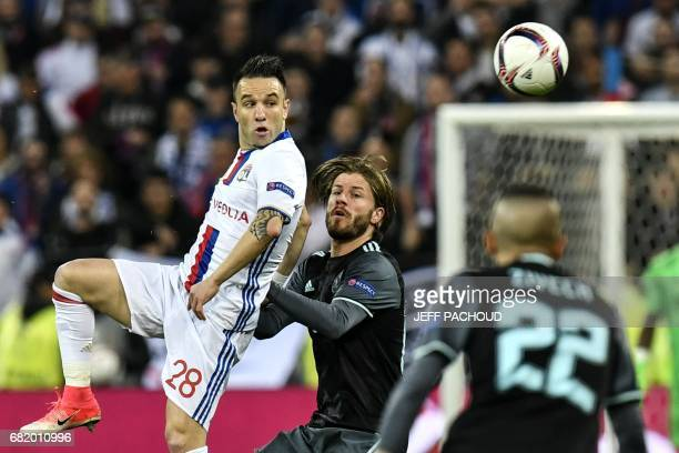 Lyon's French forward Mathieu Valbuena vies with Ajax' Danish forward Lasse Schöne during the Europa League semi final football match Olympique...