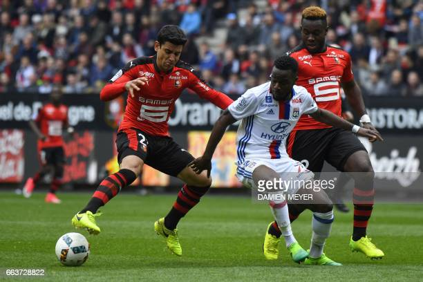 Lyon's French forward Maxwell Cornet vies with Rennes' French midfielder Benjamin Andre during the French L1 football match between Rennes and Lyon...