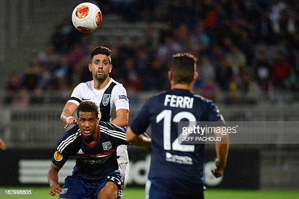 Lyon's French midfielder Alassane Plea vies for the ball with Vitoria Guimaraes' Portuguese forward Marco Matias behind Lyon's French midfielder...