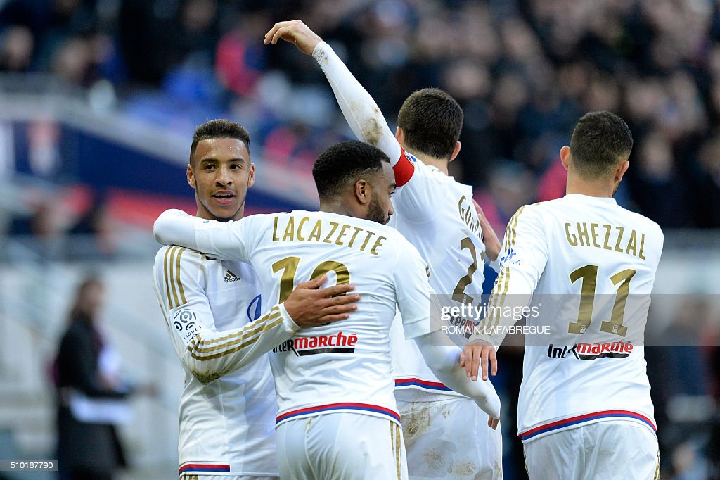 Lyon's French midfielder Corentin Tolisso (L) celebrates with teammates after scoring a goal during the French L1 football match between Olympique Lyonnais (OL) and Stade Malherbe Caen (SMC) at the Parc de l'Olympique Lyonnais in Decines-Charpieu, central eastern France, on February 14, 2016. / AFP / ROMAIN LAFABREGUE