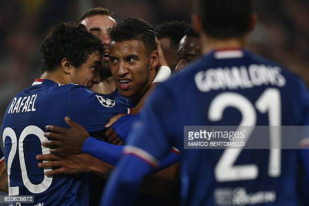 Lyon's French midfielder Corentin Tolisso is congratulated by teammate Lyon's Brazilian defender Rafael Da Silva after scoring a goal during the UEFA...