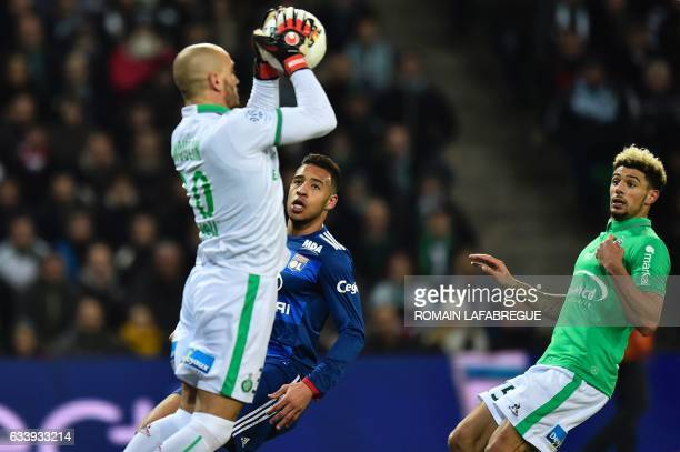 Lyon's French midfielder Corentin Tolisso looks on as SaintEtienne's French goalkeeper Jessy Moulin stops the ball in front of SaintEtienne's French...