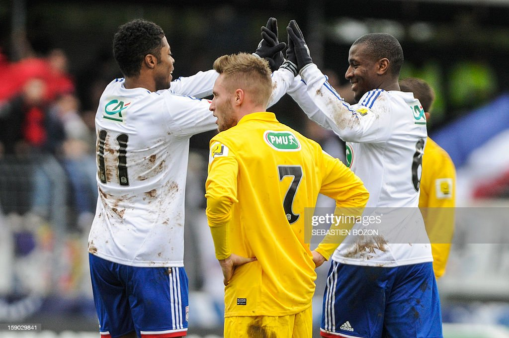 Lyon's French midfielder Gueida Fofana (R) is congratulated after scoring a goal by Lyon's Brazilian midfielder Michel Fernandes Bastos (L) during their French cup football match Epinal (SAS) versus Lyon (OL) at the Colombiere Stadium in Epinal, on January 6, 2013.