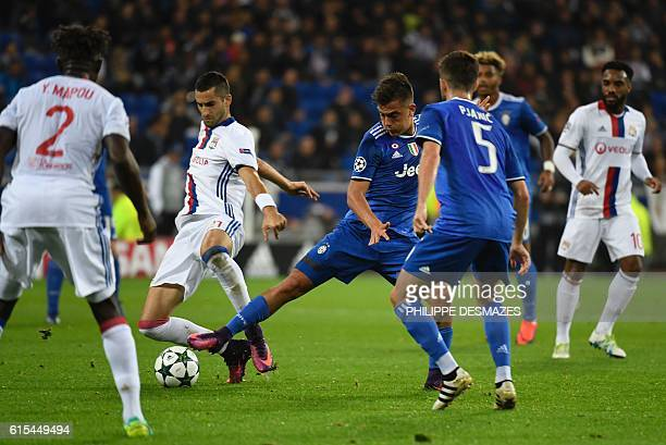 Lyon's French midfielder Maxime Gonalons vies for the ball Juventus' forward from Argentina Paulo Dybala during the Champions League football match...