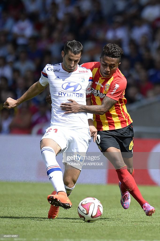 Lyon's French midfielder Maxime Gonalons (L) vies for the ball with Lens' Madagascan midfielder Lalaina Nomenjanahary (R) during the French L1 football match between Lyon (OL) and Lens (RCL) at the Gerland stadium in Lyon, central-eastern France, on August 24, 2014. AFP PHOTO / ROMAIN LAFABREGUE