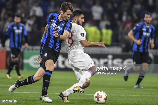 Lyon's French midfielder Nabil Fekir fights for the ball against Atalanta's Dutch midfielder Marten De Roon during the Europa League football match...