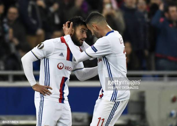 Lyon's French midfielder Nabil Fekir is congratuled by teamate Lyon's French Algerian midfielder Rachid Ghezzal after scoring during the Europa...