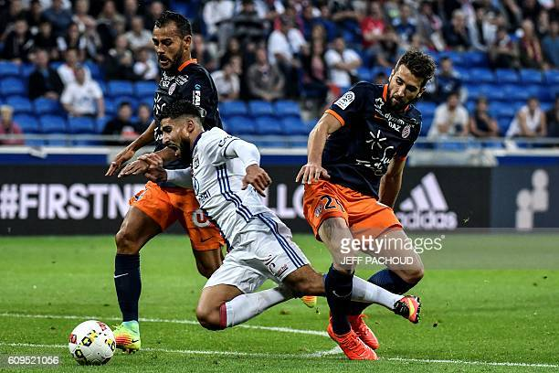 Lyon's French midfielder Nabil Fekir is tackled by Montpellier's French defender Mathieu Deplagne and Montpellier's Brazilian defender Vitorino...