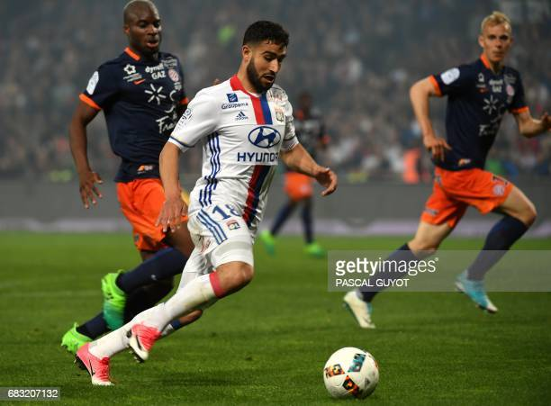 Lyon's French midfielder Nabil Fekir vies with Montpellier's Malian midfielder Yacouba Sylla and Montpellier's Czech defender Lukas Pokorny during...