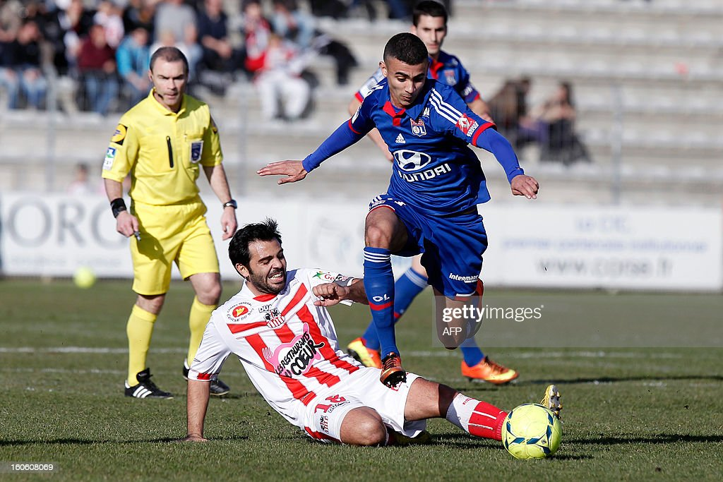 Lyon's French midfielder Rachid Ghezzal (C) vies with Ajaccio's French midfielder Johan Cavalli (bottom) during the French L1 football match Ajaccio (ACA) vs Lyon (OL) in the Francois Coty stadium in Ajaccio, French Mediterranean island of Corsica, on February 3, 2013.