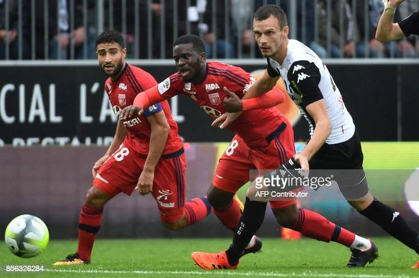 Lyon's French midfielder Tanguy Ndombele and Lyon's French midfielder Nabil Fekir vies with Angers' French defender Vincent Manceau during the French...