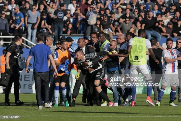 Lyon's FrenchPortuguese defender Anthony Lopes is held by security staff members as he clashes with Bastia's officials during the halftime the French...