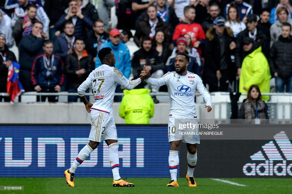Lyon's French forward Maxwell Cornet (L) celebrates after scoring a goal with Lyon's French forward Alexandre Lacazette during the French L1 football match between Olympique Lyonnais (OL) and Stade Malherbe Caen (SMC) at the Parc Olympique Lyonnais stadium in Decines-Charpieu, central-eastern France on February 14, 2016. / AFP / ROMAIN LAFABREGUE