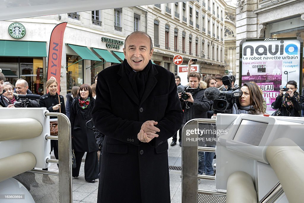 Lyon's mayor Gerard Collomb (C) gets into the urban driverless shuttle 'NAVIA' during its launch on march 13, 2013 in the east-central French city of Lyon. NAVIA is a driverless 8 passenger robotized shuttle, design for transportation in city centers. This shuttle is equipped with laser range finders, cameras and a software package that allows it to move autonomously and safely in any environment.