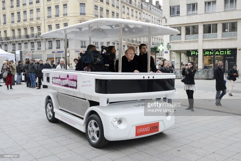 Lyon's mayor Gerard Collomb (C) is seated in the urban driverless shuttle 'NAVIA' during its launch on march 13, 2013 in the east-central French city of Lyon. NAVIA is a driverless 8 passenger robotized shuttle, design for transportation in city centers. This shuttle is equipped with laser range finders, cameras and a software package that allows it to move autonomously and safely in any environment.