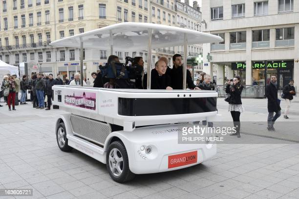 Lyon's mayor Gerard Collomb is seated in the urban driverless shuttle 'NAVIA' during its launch on march 13 2013 in the eastcentral French city of...