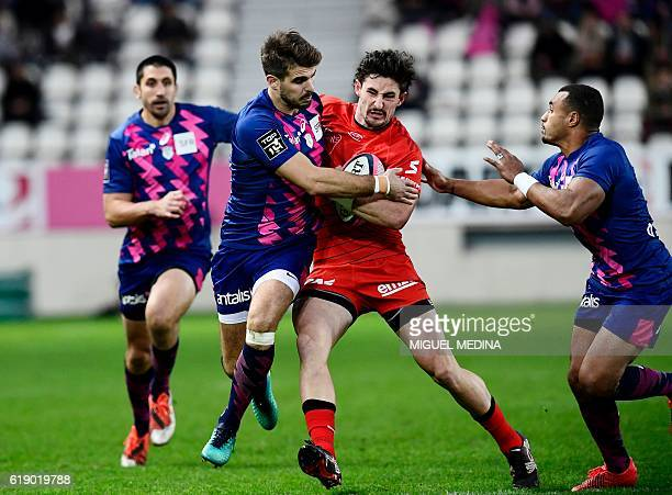 Lyon's New Zealander winger Henry CluniesRoss is tackled by Stade Francais' French fullback Hugo Bonneval and Stade Francais Paris' Australian...