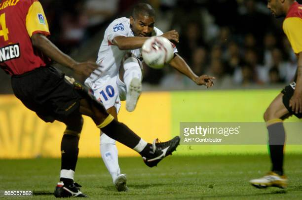 Lyon's player Florent Malouda tries to score past Lens' players during their French L1 football match 9 May 2007 at Gerland stadium in Lyon AFP PHOTO...