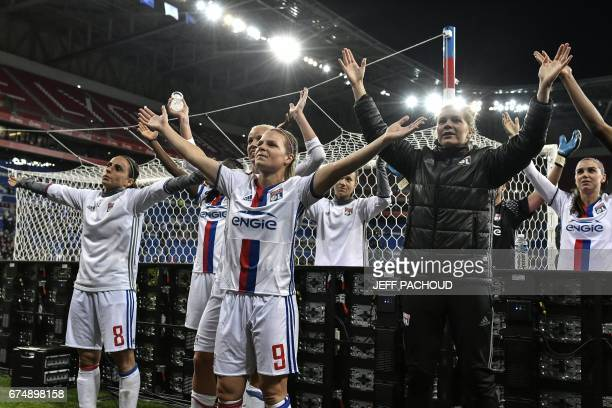 Lyon's players celebrate at the end of the UEFA Women's Champions League semifinal football match between Lyon and Manchester City at the Parc...