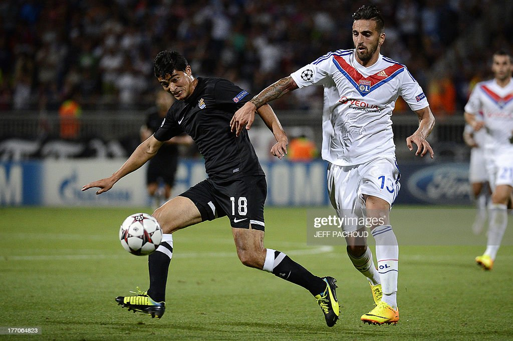 Lyon's Portuguese defender Miguel Lopes (R) vies with Real Sociedad's Uruguaian Midfielder Gonzalo Castro (L) during the first leg of the UEFA Champions League's playoffs football match Olympique Lyonnais vs Real Sociedad on August 20, 2013 at the Gerland stadium in Lyon, eastern France. AFP PHOTO / JEFF PACHOUD