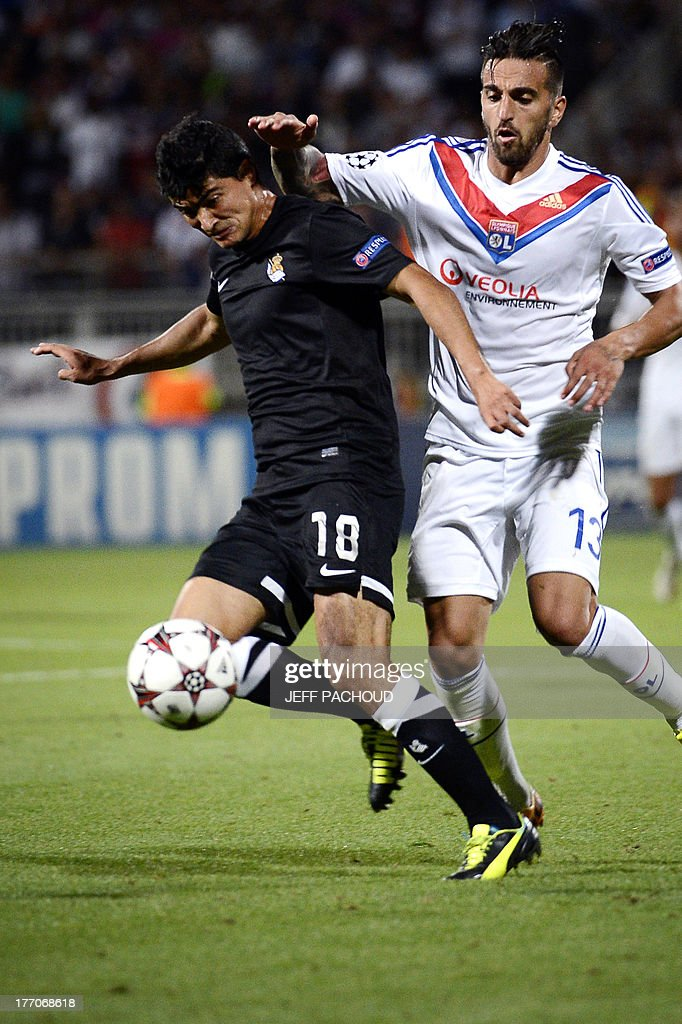Lyon's Portuguese defender Miguel Lopes (R) vies with Real Sociedad's Uruguaian Midfielder Gonzalo Castro (L) during the first leg of the UEFA Champions League's playoffs football match Olympique Lyonnais vs Real Sociedad on August 20, 2013 at the Gerland stadium in Lyon, eastern France.