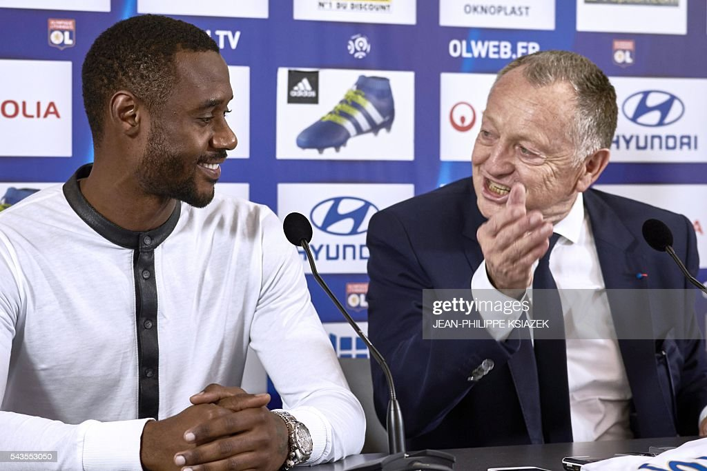 Lyon's president Jean Michel Aulas (R) gestures as Olympique Lyonnais' football club new player cameroonian Nicolas Nkoulou (L) answers journalists during his official presentation in Lyon on June 29, 2016. / AFP / JEAN