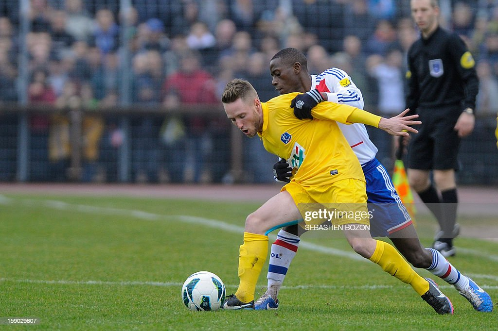 Lyon's Senegalese defender Mouhamadou Dabo (R) vies with Epinal's French midfielder Valentin Focki (2nd R) during their French cup football match Epinal (SAS) versus Lyon (OL) at the Colombiere Stadium in Epinal, on January 6, 2013.