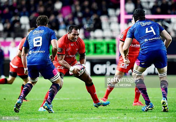 Lyon's Tongan flanker Taïasina Tuifua vies with Stade Francais Paris' South African Number Eight Jono Ross and Stade Francais Paris' Australian lock...
