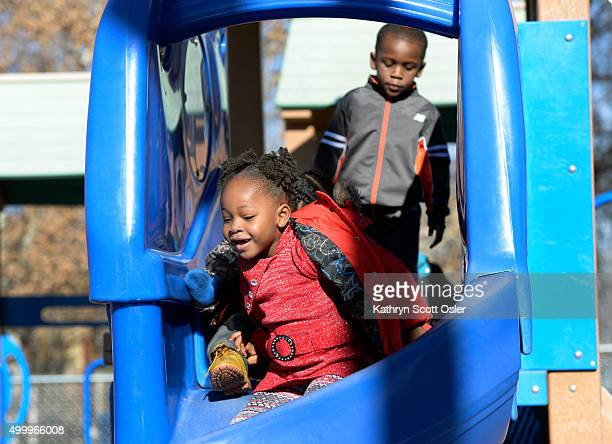 Lyric Johnson left and Michael Tann take turns on the slide on the playground on the campus of the Clayton Early Learning Center The children and...